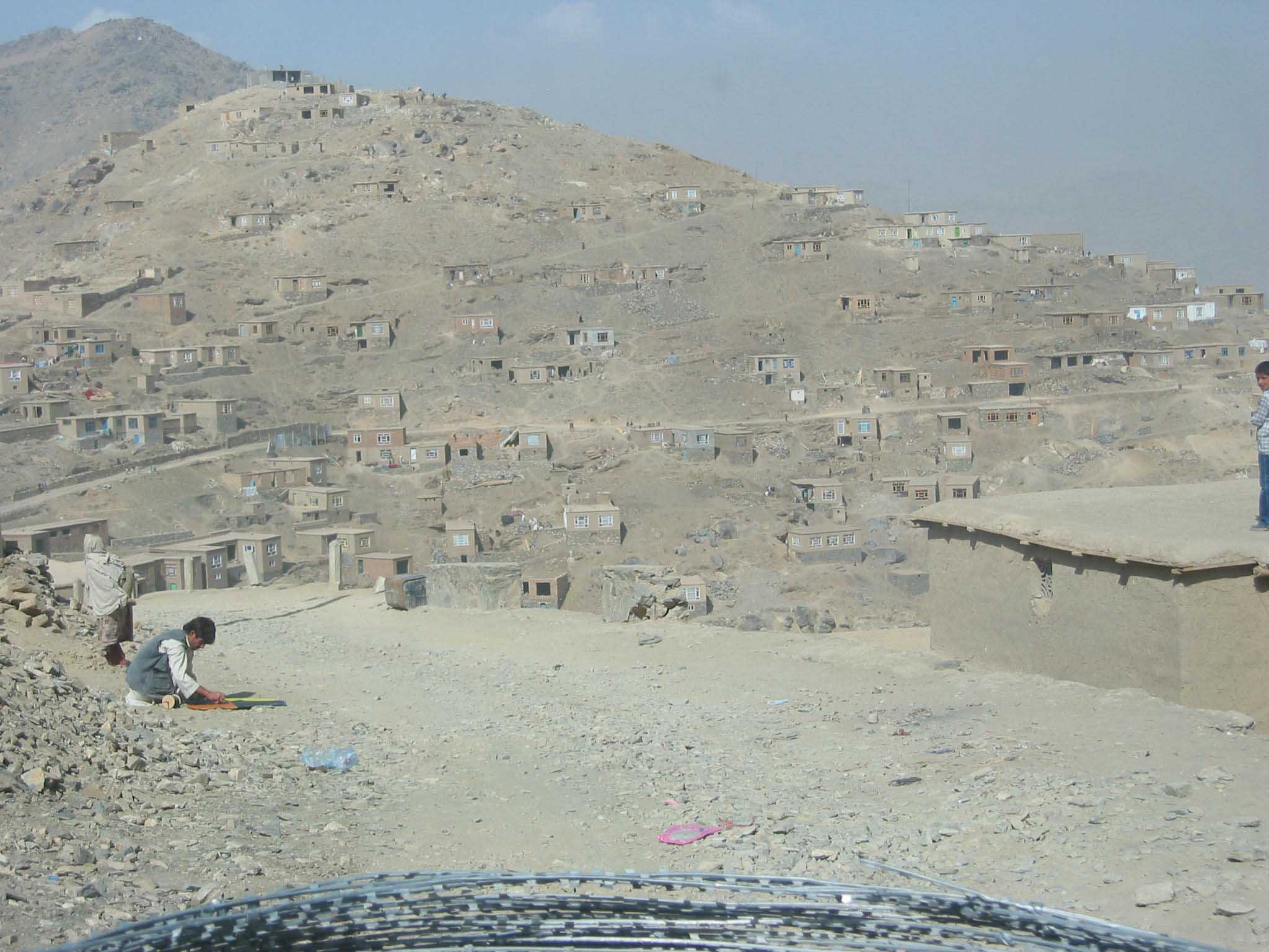 Some of houses dotted over what the range of hills which bisects Kabul in Afghanistan. The  barbed wire on the bonnet of the vehicle was intended to discourage suicide bombers from  jumping on board.