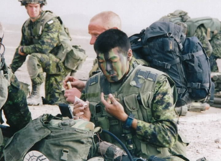 Canadian soldiers apply cam-cream in Afghanistan